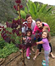 Two pretty moms and three happy kids pose by a newly planted tree